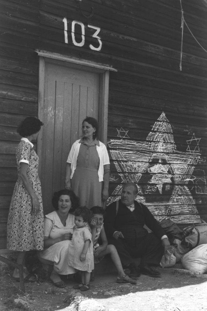 "Three women, two children and an elderly man gather, chatting, at the entrance of a large wooden building labeled ""103."" Stars of David are drawn on the building's wooden exterior in chalk."