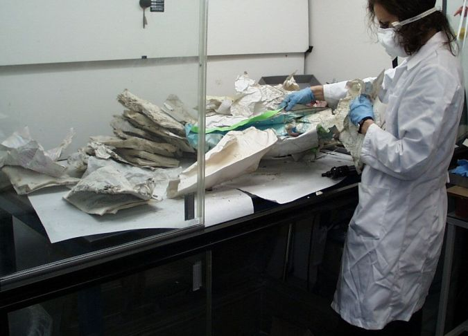 A conservator asses items from the Iraqi Jewish Archive at the National Archives.