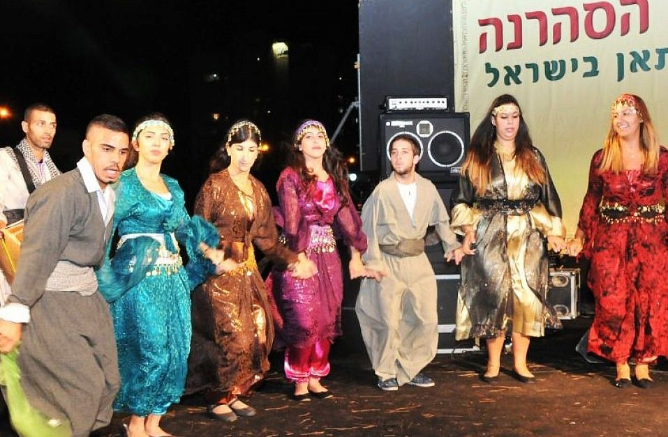 Youth dressed in traditional Kurdish clothing, long robes and colorful robe-like dresses, joining hands onstage. A sound system and banner in Hebrew is visible behind them.